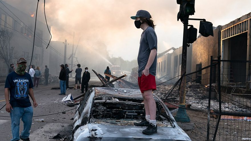 1024px-A_man_stands_on_a_burned_out_car_